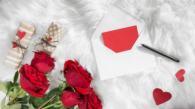 Envelope near pen, paper hearts, gifts and fresh flowers on woolen coverlet