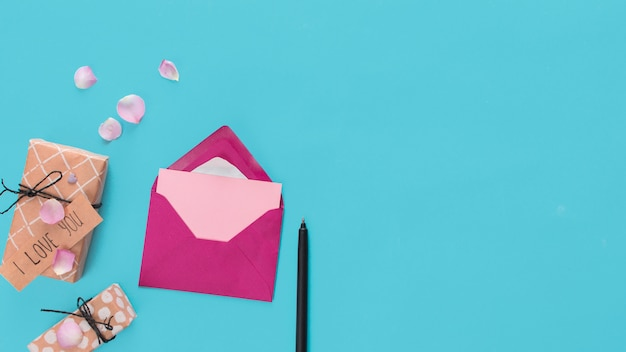Envelope near present boxes with tag, pen and petals