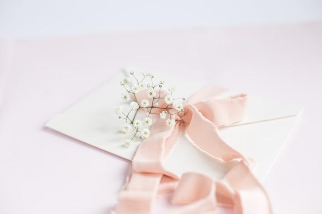 Конверт на бело-розовом фоне с персиковой шелковой лентой и розовыми цветами. приглашение на свадьбу. открытка ко дню матери. место для текста. скопируйте пространство.