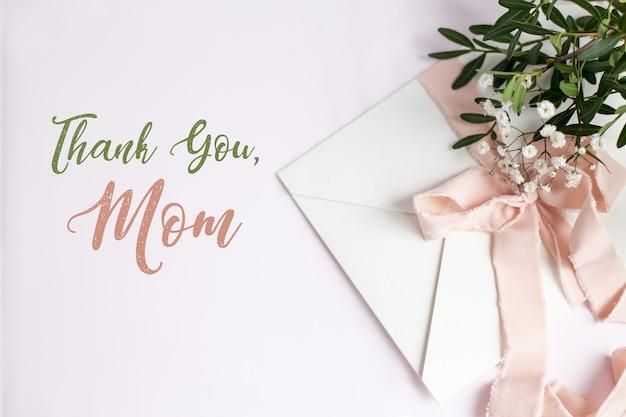 Конверт на бело-розовом фоне с персиковой шелковой лентой, зеленой веткой и цветами. открытка ко дню матери.
