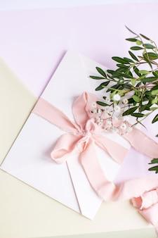 Конверт на бело-розовом фоне с персиковой шелковой лентой, зеленой веткой и цветами. приглашение на свадьбу. открытка ко дню матери. место для текста. скопируйте пространство.