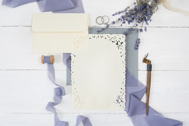 Envelope and ribbon with two wedding rings with lavender flowers and calligraphic pen