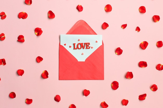 Envelope rose petals and red hearts on pink background