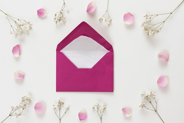 Envelope between set of fresh rose petals and plant twigs