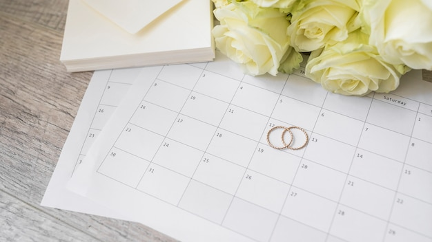Envelope stack; roses and wedding rings on calendar over wooden table