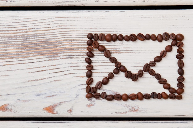 Envelope symbol made of coffee beans on white wood. brown grains arranged in a shape of mail envelope.