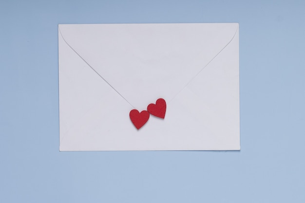Envelope and two red hearts on blue background . gift, message for lover. valentine day greeting concept.