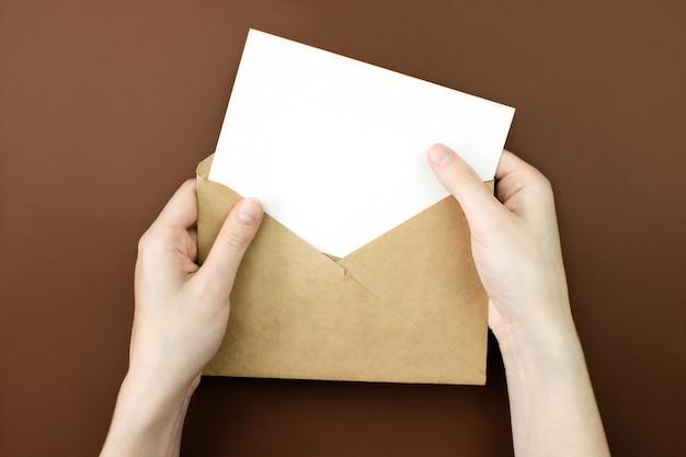 封筒、手に白い空の文字のモックアップ