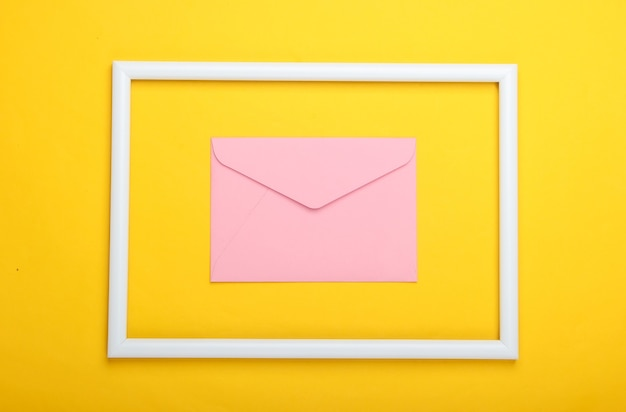 Envelope in a white frame on a yellow surface