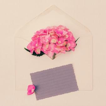 デザインのためのコピースペースとピンクのアジサイの花束と封筒。