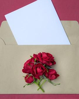 デザインのためのスペースと赤茶バラの花束と封筒