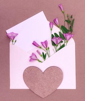 ハートとデザインのためのコピースペースを持つ野生の花の花束と封筒。