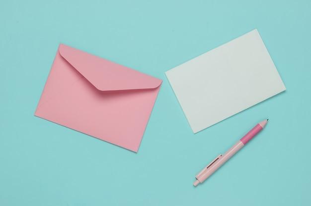 Конверт с письмом и ручкой на синем пастельном фоне. день святого валентина, свадьба или день рождения. вид сверху
