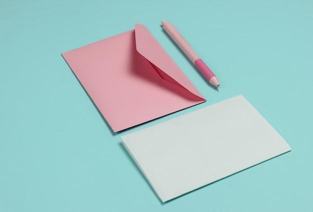Конверт с письмом и ручкой на синем пастельном фоне. день святого валентина, свадьба или день рождения
