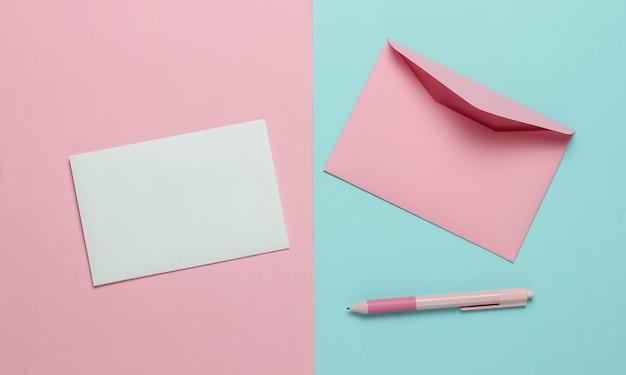 Конверт с письмом и ручкой на голубом розовом пастельном фоне. день святого валентина, свадьба или день рождения. вид сверху