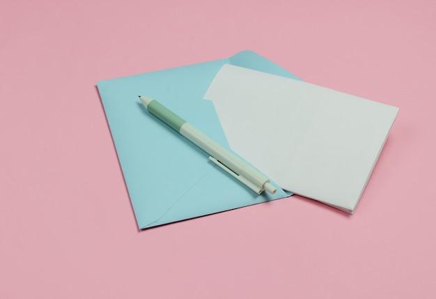 Конверт с письмом и ручкой на розовом пастельном фоне. день святого валентина, свадьба или день рождения