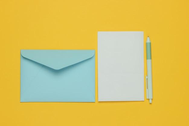 Конверт с письмом и ручкой на желтом фоне. день святого валентина, свадьба или день рождения. вид сверху