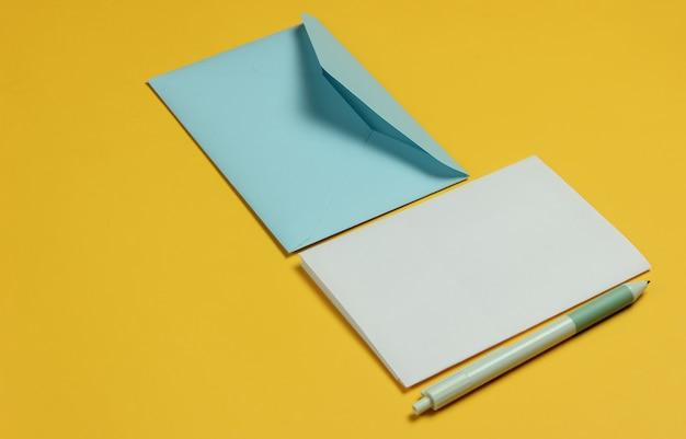 Конверт с письмом и ручкой на желтом фоне. день святого валентина, свадьба или день рождения.