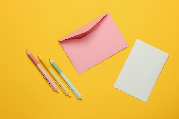 Конверт с письмом и ручками на желтом фоне. день святого валентина, свадьба или день рождения. вид сверху