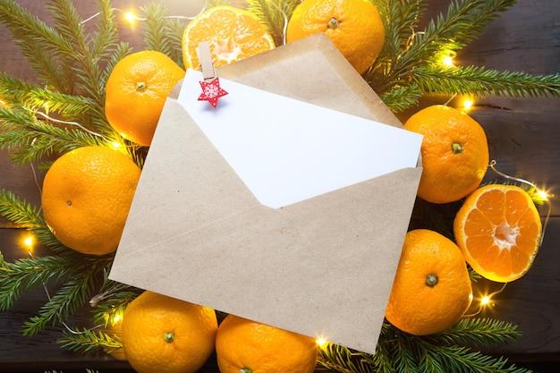 Конверт с листом бумаги-письмо деду морозу, copyspace на новогоднем фоне из мандаринов, гирлянд, еловых веток.