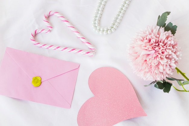 Envelope with big pink paper heart on table