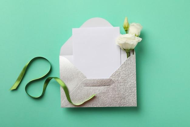 ミントの背景に空白のカード、バラ、緑のリボンと封筒