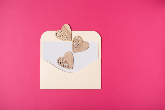 An envelope with a blank sheet of paper inside with hearts on it on the hot pink background. valentine's day concept. flat lay, top view.