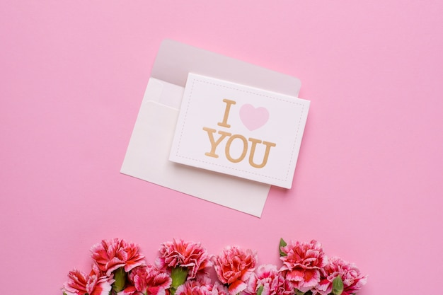 An envelope with card i love you and pink flowers on pink