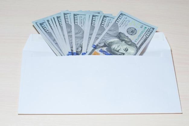 Конверт с долларовыми купюрами на деревянном столе