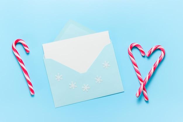 겨울 휴가 인사말과 사탕 지팡이를 위한 빈 카드가 있는 봉투