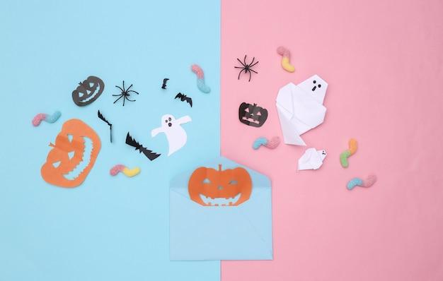 수제 할로윈 종이 장식이 있는 봉투, 분홍색 파란색 파스텔 배경에 거미 벌레. 평면도