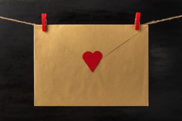 로프 문자열 말뚝에 clothespins 매달려 마음으로 봉투. 사랑하는 사람들을위한 편지. 발렌타인 데이. 검정색 배경.
