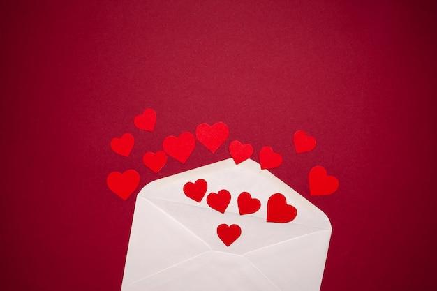 Конверт с сердечками на красном фоне. романтика и концепция любви
