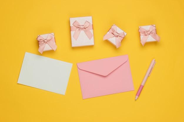 편지와 펜, 노란색 배경에 선물 상자 봉투. 크리스마스, 발렌타인 데이, 생일. 평면도