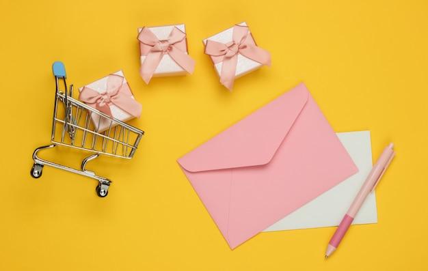 편지와 펜, 선물 상자, 노란색 배경에 쇼핑 트롤리 봉투. 크리스마스, 발렌타인 데이, 생일. 평면도