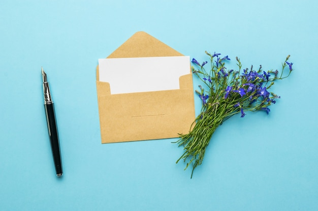An envelope with a letter, a fountain pen and a bouquet of flowers on a blue background. flat lay.