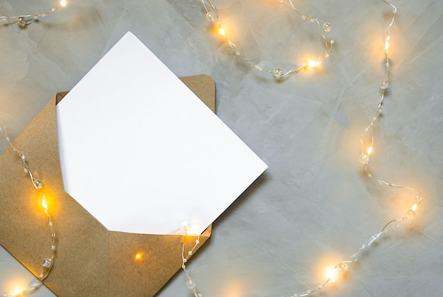 Envelope with a letter lies on grey backgroun with a christmas garland.