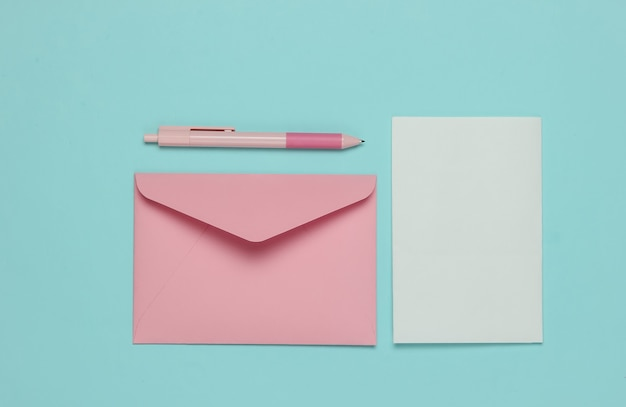Envelope with a letter and pen on a blue pastel background. valentine's day, wedding or birthday. top view