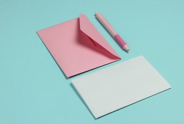 Envelope with a letter and pen on a blue pastel background. valentine's day, wedding or birthday
