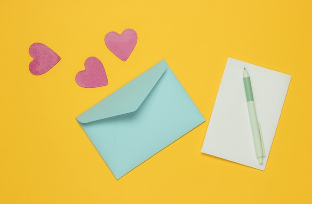 Envelope with a letter, pen, decorative hearts on yellow background. flat lay mockup for valentine's day, wedding or birthday.