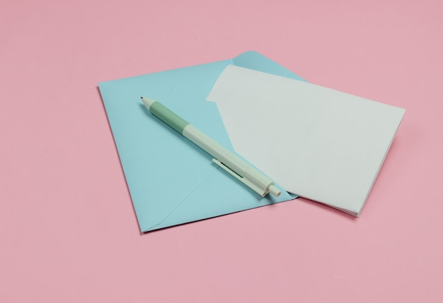 Envelope with a letter and pen on pink pastel background. valentine's day, wedding or birthday