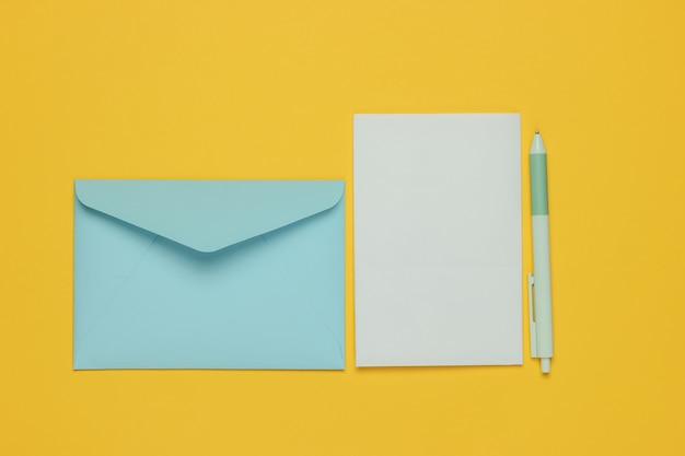 Envelope with a letter and pen on yellow background. valentine's day, wedding or birthday. top view