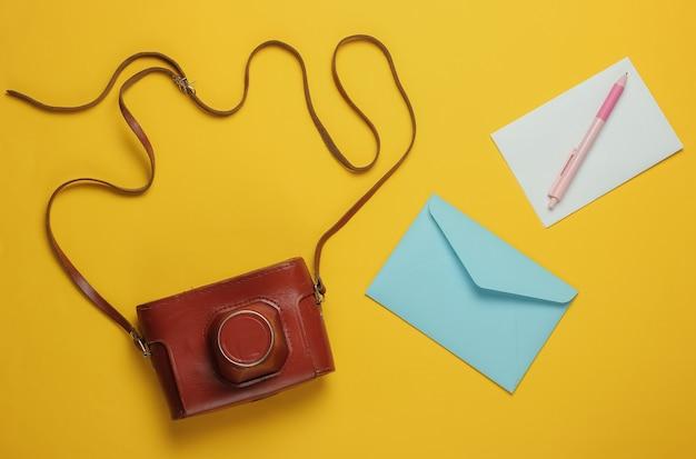 편지, 노란색 배경에 레트로 카메라 봉투. 평면도. 여행 컨셉