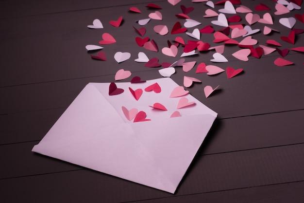 Конверт с бумажными сердечками на сером деревянном