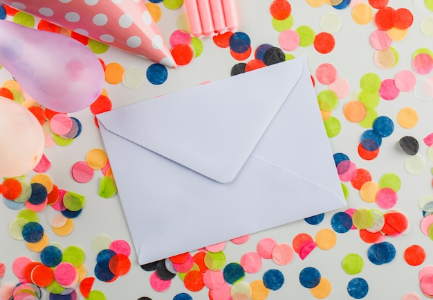 Envelope with party decorations on a white table