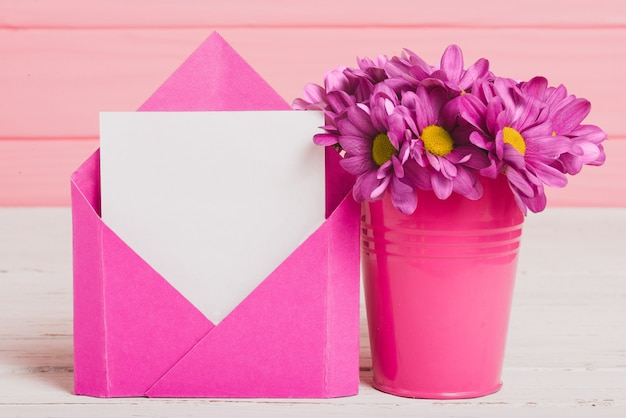 Envelope with piece of paper and beautiful purple flowers