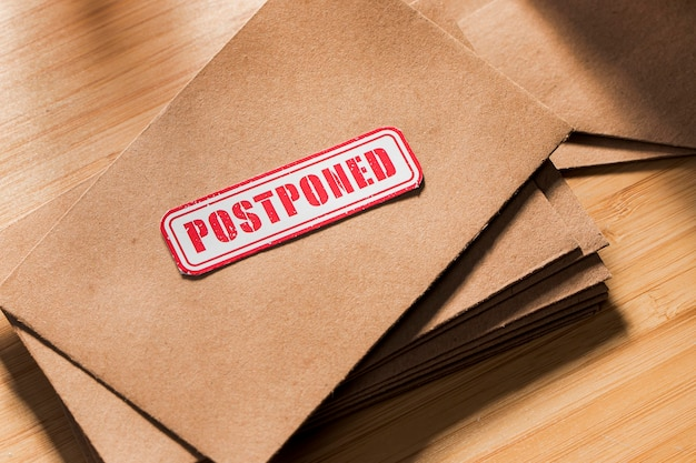 Envelope with postponed message on table