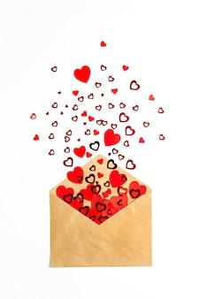 Конверт с красными сердечками на белой поверхности. плоская планировка, вид сверху