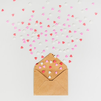 Envelope with small paper hearts on white table