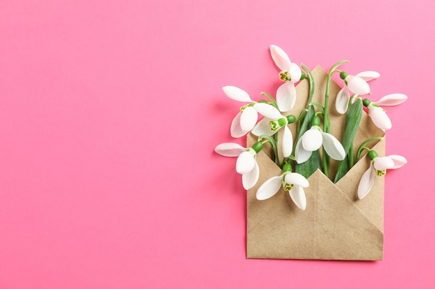 Envelope with snowdrop flowers on color background, space for text